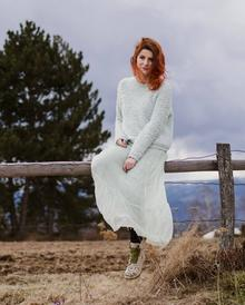 Mihaela, sitting on a fence in the countryside, with melancholic clouds overhead